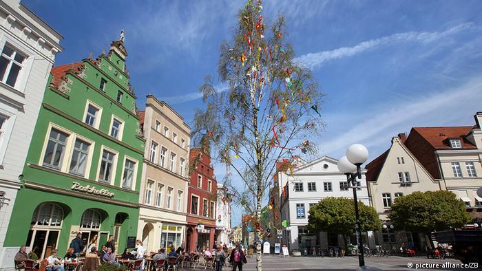 Auf dem Platz einer kleinen Stadt steht ein festlich geschmückter Maibaum