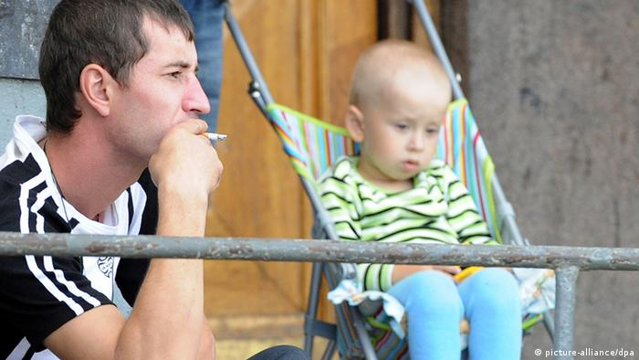 A Russian man smoking a cigarette next to a child (Photo ITAR-TASS/ Artyom Korotayev)