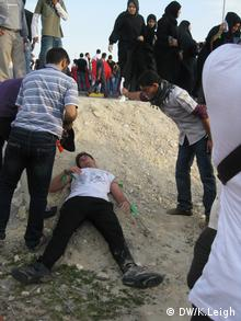 A Riffa protester recovers from tear gas