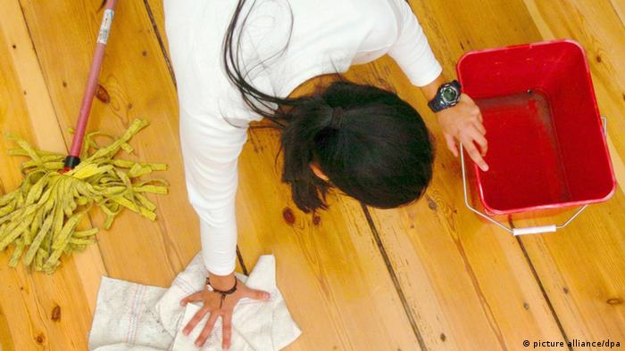 A woman cleans a wooden floor