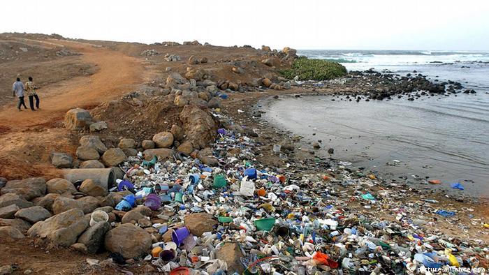 Men walk past a polluted river bank leading into the Atlantic ocean off Dakar, Senegal