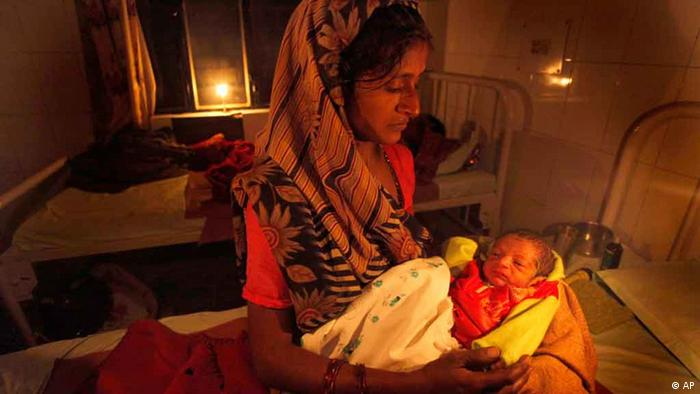 An Indian mother tends to her new born baby under a candle light during a power cut