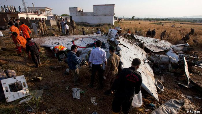 Paramilitary soldiers and members of the media gather near the wreckage of a Boeing 737 airliner that crashed in Islamabad
