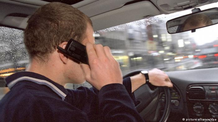 Ein Autofahrer während der Fahrt mit einem Mobiltelefon
