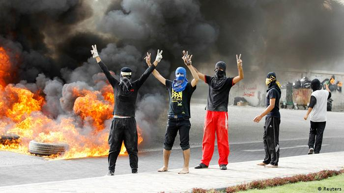 Anti-government protesters flash victory signs as they burn tires