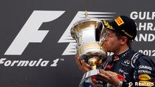 Red Bull Formula One driver Sebastian Vettel of Germany kisses his trophy after winning the Bahrain F1 Grand Prix at the Sakhir circuit in Manama April 22, 2012. REUTERS/Steve Crisp (BAHRAIN - Tags: SPORT MOTORSPORT TPX IMAGES OF THE DAY)