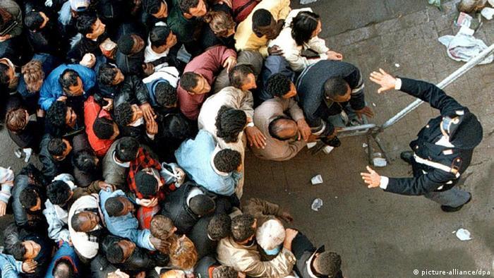 Ein italienischer Polizist versucht hunderte von illegale Einwanderer zu beruhigen. (Foto: dpa)