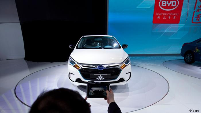 A man takes photos of the newly-unveiled BYD Qin at the Beijing International Auto Exhibition in Beijing, China, Monday, April 23, 2012. (AP Photo/Alexander F. Yuan)
