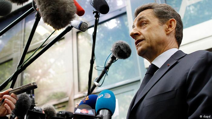 Nicolas Sarkozy speaks to reporters' microphones