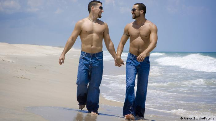 Ein schwules Paar geht Hand in Hand am Strand spazieren
