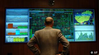 Сотрудник газовой компании на фоне мониторов с информацией о поставках и распределении газа