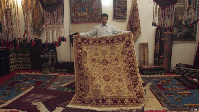 An Afghan shopkeeper displays an Afghani hand-made carpet at the joint Iran-Afghanistan exhibition in the city of Herat province, southwest of Kabul, Afghanistan on Monday, Oct 29, 2007. (ddp images/AP Photo/Fraidoon Pooyaa)