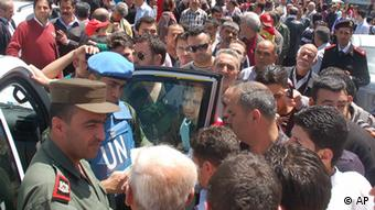 A UN observer and Syrian army officer listen to Syrian citizens
