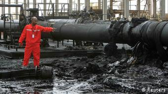 A Sudanese engineer points at the damage to an oil pipeline in a largely damaged oilfield in Heglig.