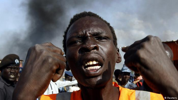 A man gestures at a market burnt in an air strike by the Sudanese air force