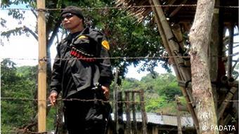 Ein schwarz angezogener Sicherheitsmann patroulliert hinter Stacheldrahtzaun auf der Ranch von Ernesto Villalon im Minanao (Foto: Padata)