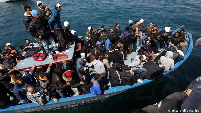 A boot full of refugees off the coast of the Italian island of Lampedusa
