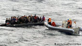 A group of refugees in a rickety boat being rescued by a Coast Guard patrol