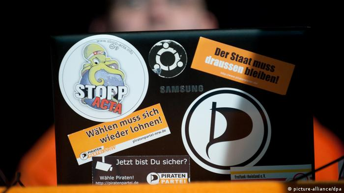 A Pirate Party member's laptop, viewed from behind, with a series of stickers on the lid. The user is visible, but obscured in the background.