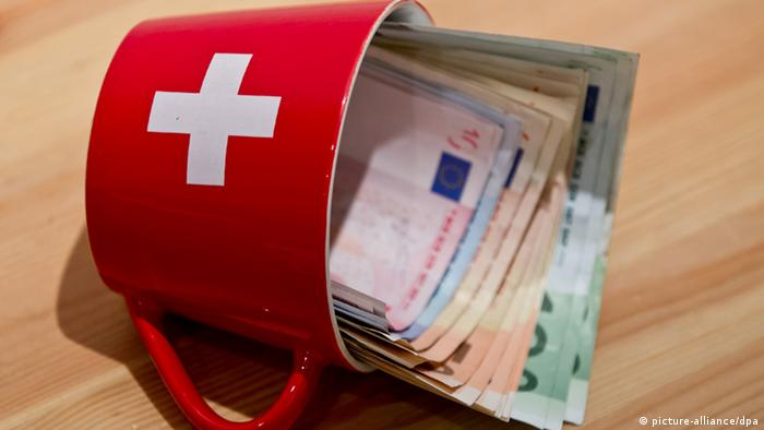 Euro banknotes in a cup showing the Swiss flag