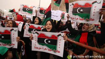 Libyans wave Libya flags and anti-federalization signs during a protest