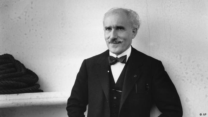 Black-and-white photo of Arturo Toscanini, mustachioed and smiling as though triumphantly holding a secret (AP)
