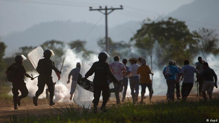 Amidst tear gas, police officers chase protesters during clashes after a march on the outskirts of Yucumo, Bolivia, Sunday Sept. 25, 2011. Indigenous and environmentalist groups began the Aug. 15th march to La Paz in protest of the government's planned highway that would cut through the nature preserve, Territorio Indígena Parque Nacional Isiboro Sécure or TIPNIS, home to 15,000 natives. (Foto:Juan Karita/AP/dapd)
