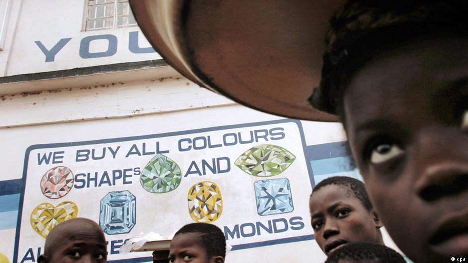 Child miners near a painting of we buy all colors on the wall in Kenema (Photo: Les Stone)