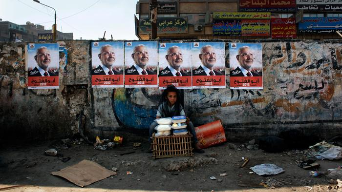 An Egyptian girl street vendor displays dairy products for sale under electoral posters