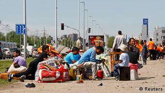 Roma people sit on the sidewalk as they wait to be evacuated from a slum in Belgrade April 26, 2012. (Photo: REUTERS/Ivan Milutinovic)