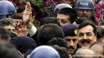 Former Pakistani Prime Minister Yusuf Raza Gilani (R) waves to his supporters upon arrival at the Supreme Court