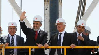 Turkish Energy Minister Taner Yildiz, second left, waves to the media next to Turkish Cypriot leader Dervis Eroglu, second right, from the drilling platform during a ceremony marking the start of exploratory oil and gas drilling by Turkey in breakaway Turkish Cypriot northern half of ethnically split Cyprus, near Sinirustul/Syngkrasi, village, on Thursday, April 26, 2012. The move counters an offshore gas search by rival Greek Cypriots in the island's internationally recognized southern half that has touched off vociferous protests from Ankara and Turkish Cypriots. (Foto:Petros Karadjias/AP/dapd).