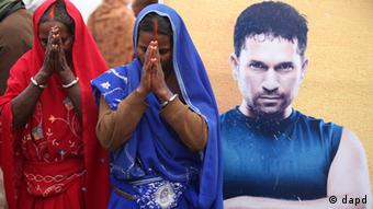 Hindu women devotees offer prayers, besides a poster of cricketer Sachin Tendulkar, on the banks of the Rivers Ganges