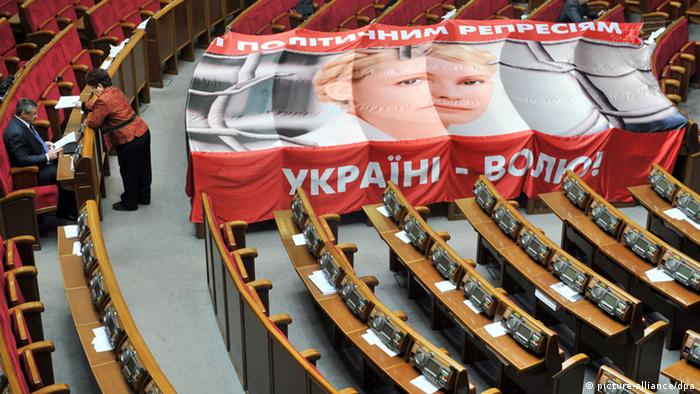 Member of Ukraine's parliamentary opposition stand by a giant placard depicting former Prime Minister Yulia Tymoshenko, and reading Stop political repressions! and Free Ukraine