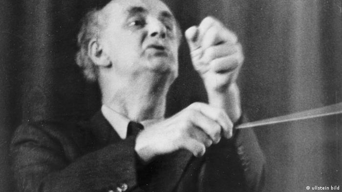 Wilhelm Furtwängler conducting, one hand clenched in a fist, the other waving a baton, eyes beseeching (ullstein bild)