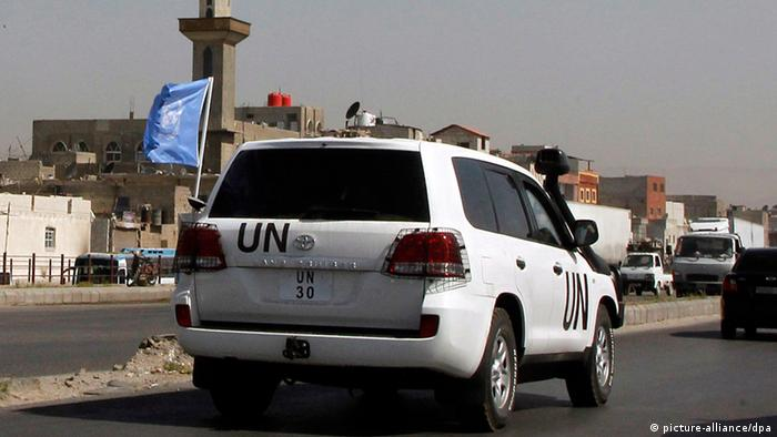 A car carrying UN observers drives on a road leading to Douma and Harasta, om eastern Damascus,