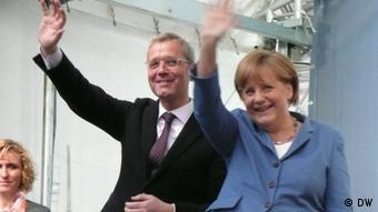 Röttgen and Merkel waving to CDU supporters