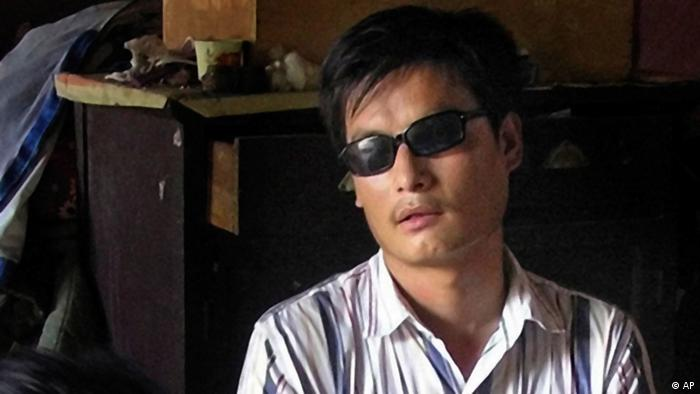 FILE - In this undated file photo released by his supporters, blind activist Chen Guangcheng, right sits in a village in China. Rights activists have criticized a Hollywood studio for filming a buddy comedy in an eastern Chinese city where the blind, self-taught activist lawyer is being held under house arrest and reportedly beaten. Relativity Media is shooting part of the comedy 21 and Over in Linyi, a city in Shandong province where the activist Chen's village is located. Authorities have turned Chen's village of Dongshigu into a hostile, no-go zone and activists, foreign diplomats and reporters have been turned back, threatened and had stones thrown at them by men patrolling the village. (AP Photo/Supporters of Chen Guangcheng, File)