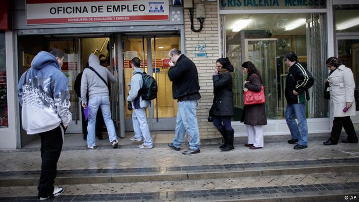 People queue outside an unemployment registry office in Madrid