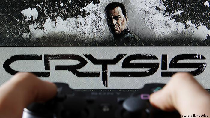 Zwei Hände bedienen ein Joypad vor einem Bildschirm mit einer Szene des Spiels Crysis (Foto: DPA)