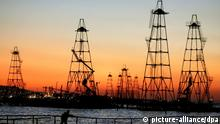 The sun rises behind the oil derricks on the Caspian Sea near Baku, Azerbaijan, Friday 07 October 2005. More than 1,500 floatable oil derricks extract oil from Caspian's seabed in Azerbaijan. In 2005 Azerbaijan extracted 19,5 million tons of oil. Foto: SERGEI ILNITSKY +++(c) dpa - Report+++
