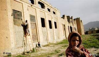 An Afghan man works to repair a window of a war damaged building