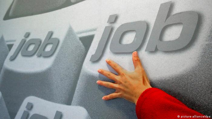 A hand touching an image of a keyboard with the word 'job' written on every key