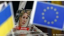 Потрет Юлии Тимошенко на фоне украинского флага и флага ЕС