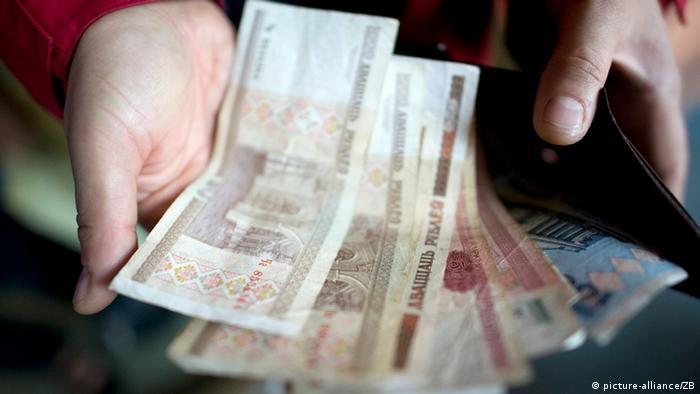 Руки, держащие белорусские рубли