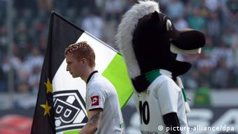 Marco Reus stands with his back to the Borussia Mönchengladbach mascot, a foal, who is holding a club flag.