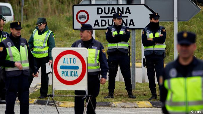 Police officers stand guard in a checkpoint near to the border of Spain and France in La Jonquera, Girona, Spain, Saturday, April 28, 2012. Spain has temporarily restored border checks in its northeast and at two major airports in a bid to stop protesters entering the country ahead of a European Central Bank meeting in Barcelona. Spanish authorities early Saturday suspended the Schengen Treaty which allows unrestricted travel inside member nations, and imposed controls at six border crossings with France and at Barcelona and Gerona international airports. (Foto:Emilio Morenatti/AP/dapd).