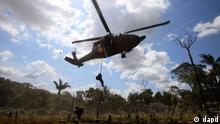 Police rappel from a helicopter to destroy a cocaine processing lab in Puerto Concordia in Colombia's southern Meta state, Wednesday Jan. 25, 2012. Police seized cocaine and chemicals at the lab that according to the commander of anti-narcotic police Gen. Luis Perez, belonged to rebels of the Revolutionary Armed Forces of Colombia, FARC. (AP Photo/Fernando Vergara)