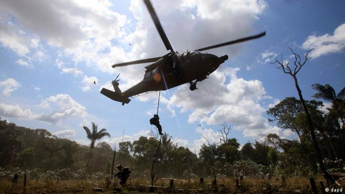 Police rappel from a helicopter to destroy a cocaine processing lab in Puerto Concordia in Colombia's southern Meta state