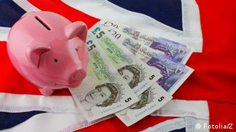 A symbol picture of a piggy bank pound notes, and the union jack flag (Photo © Z #30469496)